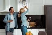 Selektivní zaměření veselého dospělého páru tančícího s sklenicemi na víno v kuchyni