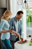 Usmívající se muž krájení zeleniny v blízkosti manželky se sklenkou vína v kuchyni