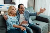 Šokovaný starší pár sledování televize doma