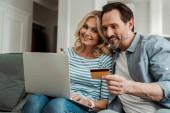 Fotografie Selektiver Fokus eines lächelnden reifen Paares mit Kreditkarte und Laptop auf der Couch