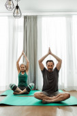 Photo Mature couple practicing yoga on fitness mats in living room