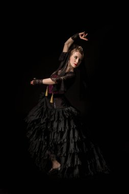 beautiful dancer looking away while dancing flamenco and gesturing isolated on black