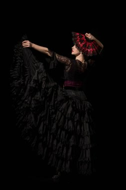young and beautiful dancer holding fan while dancing flamenco isolated on black