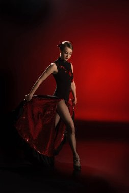 pretty flamenco dancer touching dress while dancing on red