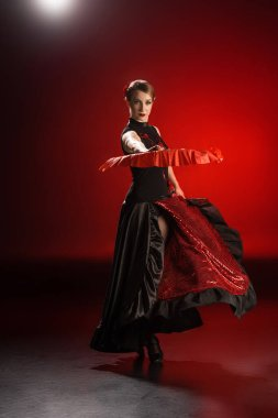 elegant woman in dress holding fan while dancing flamenco on red