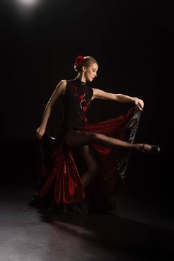 side view of young woman touching dress and dancing flamenco on black