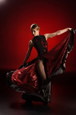 young woman touching dress and dancing flamenco on red