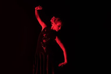 red lighting on elegant and young woman dancing flamenco isolated on black