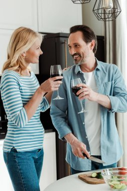 Mature couple smiling at each other while toasting with wine near fresh vegetables on kitchen table stock vector