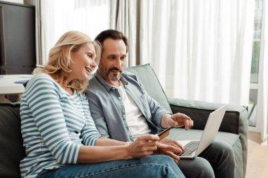 Kanepede dizüstü bilgisayar ve kredi kartı kullanan gülümseyen olgun bir çift.