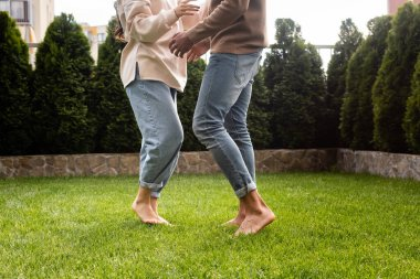 cropped view of couple dancing on green grass outside