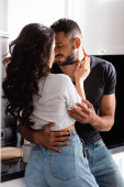 young woman hugging bearded boyfriend with closed eyes