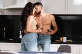 Fotografie Selektiver Fokus einer jungen Frau, die ein Glas Rotwein in der Hand hält und den hemdslosen Mann ansieht