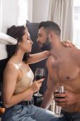 Seitenansicht eines gut aussehenden, muskulösen Mannes und einer schönen Frau mit einem Glas Rotwein