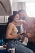 selektivní zaměření svalnatého muže a usměvavé ženy držící sklenice červeného vína