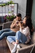 pohledný muž a atraktivní žena sedí na venkovní pohovce a pití červeného vína