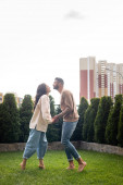 side view of beautiful woman and bearded man holding hands while standing on green grass