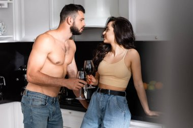 Selective focus of shirtless man and happy woman holding glasses of red wine and looking at each other stock vector