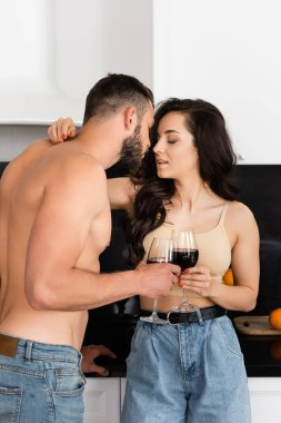 Shirtless man and attractive woman with closed eyes holding glasses of red wine stock vector
