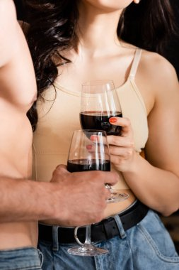 Cropped view of shirtless man and young woman holding glasses of red wine stock vector