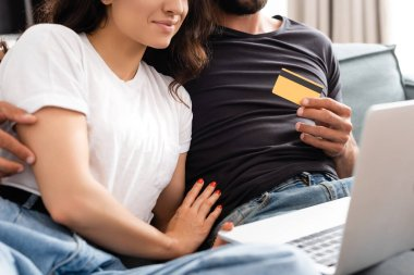 Cropped view of bearded man holding credit card and hugging happy girlfriend near laptop stock vector