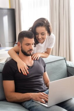 Happy woman hugging freelancer using laptop in living room stock vector