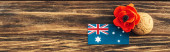 panoramic crop of australian flag near artificial flower and cookie on wooden surface