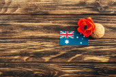 Photo top view of australian flag near artificial flower and cookie on wooden surface