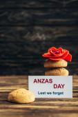 kártya anzas napi felirattal közel mesterséges virág és ízletes cookie-k fa felületen