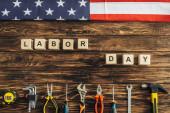 pohled shora na kovové nástroje a americkou vlajku v blízkosti kostek s nápisem pracovního dne na dřevěném povrchu