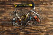 vrchní pohled na nástroje a kovové hřebíky na dřevěném povrchu, koncept pracovního dne