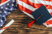 Photo top view of graduation cap and diploma near american flag with stars and stripes on wooden surface