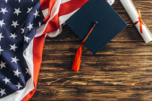 Photo top view of diploma and graduation cap near american flag with stars and stripes on wooden surface