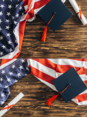 Photo collage of diploma and graduation caps near american flags with stars and stripes on wooden surface