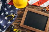 Draufsicht auf amerikanische Flagge und Instrumente in der Nähe von leerer Kreidetafel auf Holzoberfläche, Arbeitstagskonzept