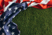 top view of american flag with stars and stripes on green grass outside, labor day concept