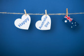 Photo rope, clothespins and heart-shaped papers with happy near australia day lettering and flag on blue