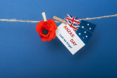 rope, clothespins and card with anzas day lettering near artificial flower and flags of australia on blue