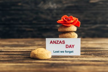 Card with anzas day lettering near artificial flower and cookies on wooden surface stock vector