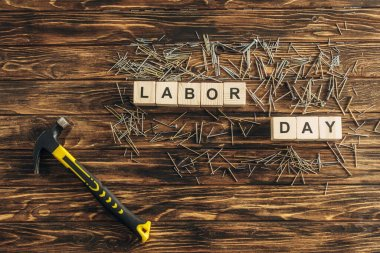 Top view of metallic nails and hammer near cubes with labor day lettering on wooden surface stock vector
