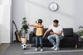 Junge im Kopfhörer steht mit ausgestreckten Händen neben Vater auf Sofa