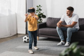 selective focus of cute boy standing and gesturing in vr headset near smiling father sitting on sofa