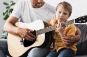 ostříhaný pohled na otce učícího syna, jak hrát na akustickou kytaru