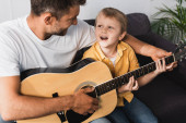 smiling father teaching excited son how to play acoustic guitar at home