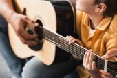 ostříhaný pohled na otce učícího syna, jak hrát na akustickou kytaru, selektivní zaměření