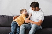 cheerful father and son having fun while jokingly fighting on sofa at home