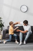 glücklicher Vater und Sohn haben Spaß beim scherzhaften Kämpfen auf dem heimischen Sofa