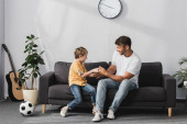 cheerful father and son jokingly fighting on sofa near potted plants, soccer ball and guitar