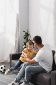 father and happy son jokingly fighting on sofa near soccer ball