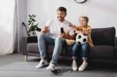 glücklicher Junge hält Fußball in der Hand und zeigt mit dem Finger auf aufgeregten Vater, während er fernsieht
